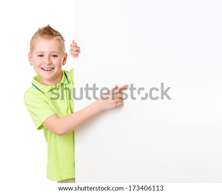 Handsome kid boy pointing to blank advertisement banner - stock photo