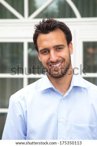 Handsome latin businessman in front of his office - stock photo