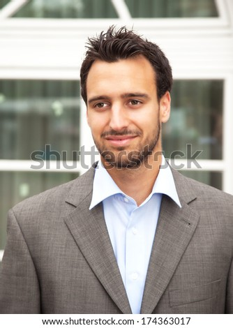 Handsome latin businessman smiling in front of his office  - stock photo