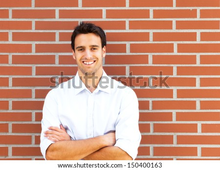 Handsome latin guy in front of a brick wall - stock photo