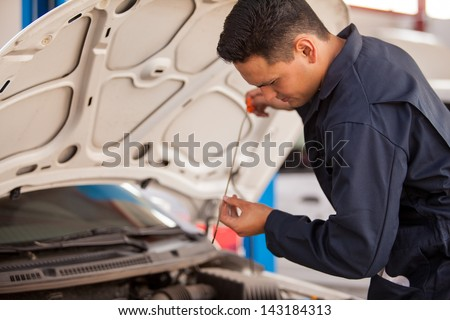 Handsome Latin mechanic measuring the oil level of an engine at an auto shop - stock photo