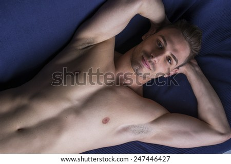 Handsome latin young man naked on floor or couch with hands under his head - stock photo