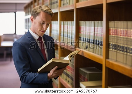 Handsome lawyer in the law library at the university - stock photo