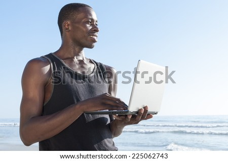Handsome lean young African American man smiles as he observes activity on beach while connected online with small laptop computer in sunny outdoors - stock photo