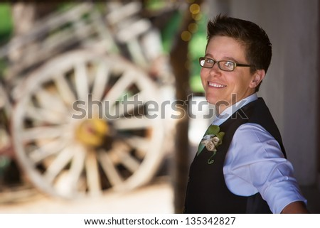 Handsome lesbian groom outdoors in vest - stock photo