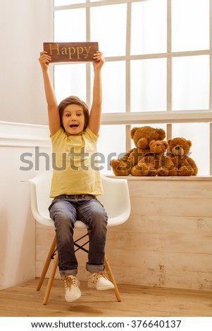 """Handsome little boy holding a wooden plate """"Happy"""", looking in camera and smiling while sitting on a chair near the window - stock photo"""