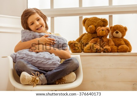 Handsome little boy hugging a cushion, looking in camera and smiling while sitting on a chair near the window - stock photo
