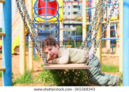 Handsome little boy lies in swings with chains on playground at summer day - stock photo