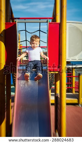 Handsome little boy playing video games outside. - stock photo