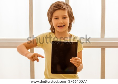 Handsome little boy pointing on a tablet, looking in camera and smiling while sitting near the window - stock photo