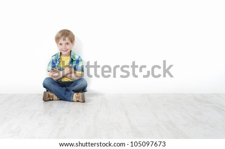 Handsome little boy sitting on floor leaning against white wall. Legs and hands crossed. - stock photo