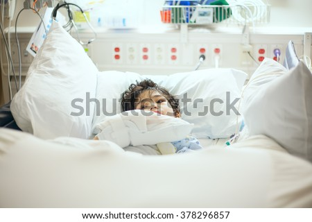 Handsome little disabled nine year old boy lying sick in hospital bed.  Child has cerebral palsy - stock photo