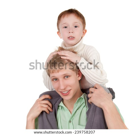 handsome little kid sitting on the neck of his elder brother - stock photo