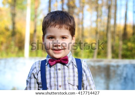 Handsome little plump boy in shirt and bow tie smiles in sunny green park - stock photo