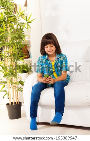 Handsome little 6 yeas old boy boy text using phone sitting on the coach looking on the screen of cellphone - stock photo