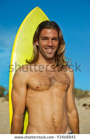 Handsome long haired blonde surfer standing in front of his surfboard. - stock photo