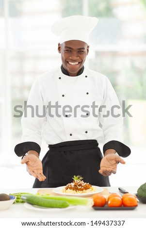 handsome male african chef presenting spaghetti in kitchen - stock photo