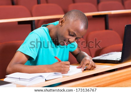 handsome male african college student writing classwork - stock photo