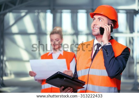 Handsome male architect in helmet is talking on the phone with his customer. He is smiling and holding a tablet. The female worker is standing behind him and looking at the blueprint seriously - stock photo