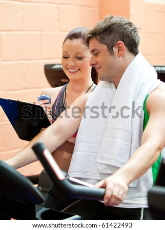 Handsome male athlete exercising on a bicycle with his personal coach in a fitness center - stock photo