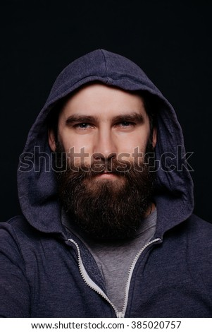 Handsome male big beard in hoodies, studio shot on black background, looking directly at the camera - stock photo