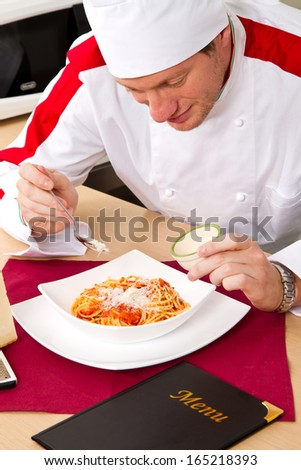Handsome male chef dressed in white uniform decorating pasta - stock photo