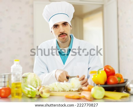 Handsome male cook does vegetarian lunch at kitchen - stock photo