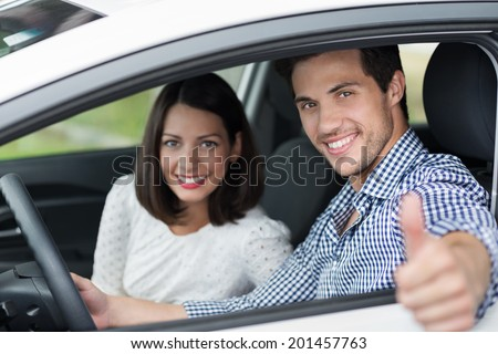 Handsome male driver giving a thumbs up through the car window as he drives along with his beautiful young wife or girlfriend as a passenger - stock photo
