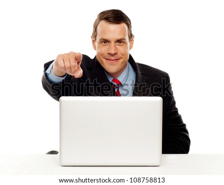 Handsome male executive pointing at you while working on laptop at his work desk - stock photo