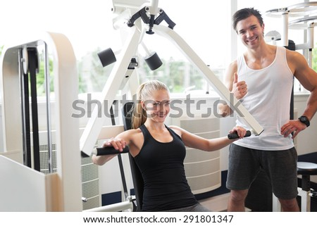 Handsome Male Fitness Trainer Smiling at the Camera while Assisting a Healthy Woman Doing Chest Press Exercise in the Gym. - stock photo