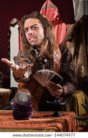 Handsome male fortune teller with tarot cards and crystal ball - stock photo