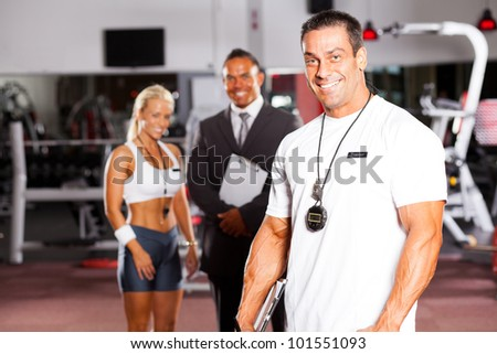 handsome male gym personal trainer in front of colleagues - stock photo