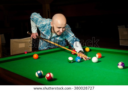 Handsome male model plays at pool billiard table. American pool billiard. Pool billiard game. Billiard sport concept. - stock photo