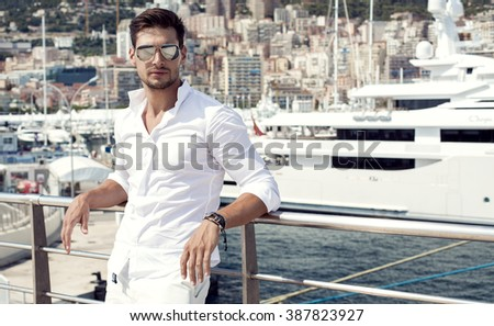Handsome male model posing in front of a luxury yacht during summer vacation - stock photo