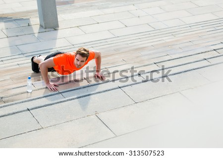 Handsome male runner in bright orange t-shirt doing push-ups on stairs in urban setting, young athletic man warm up outdoors before begin his run, copy space area for your text message or content - stock photo