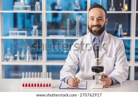 Handsome male scientist analysing something with  a microscope and doing notes in a laboratory. And looking at camera. - stock photo