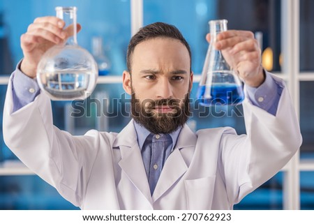 Handsome male scientist researcher observing liquid in flasks in a laboratory. - stock photo