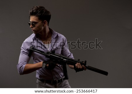 Handsome male shooter or contractor with automatic rifle - stock photo