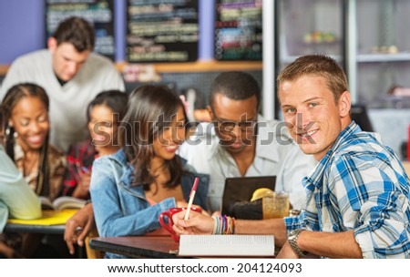 Handsome male student with friends in coffee house - stock photo