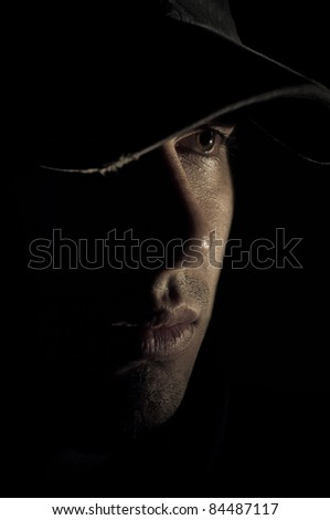 Handsome male with hat in profile. Low light portrait - stock photo