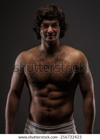 Handsome male with naked torso. Isolated on grey. - stock photo