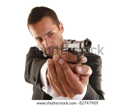 Handsome man aims with gun - stock photo