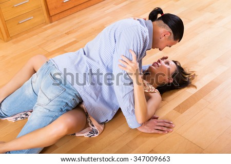 Handsome man and adult smiling female having foreplay indoor - stock photo