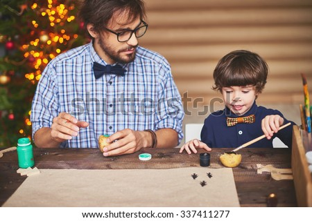 Handsome man and his son making Christmas prints - stock photo