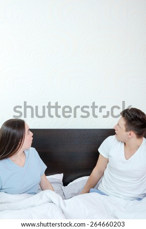 Handsome man and pretty surprised woman in bedroom looking up at thinking speech bubble, comic cloud or empty copyspace. Sexy young couple in bed, domestic atmosphere. Place for text and advertising - stock photo
