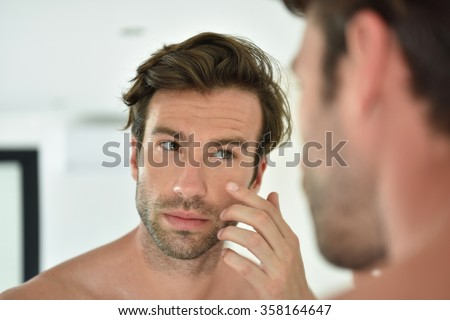 Handsome man applying facial cream in front of mirror - stock photo