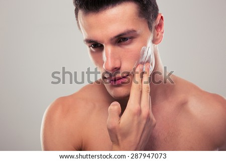 Handsome man applying facial cream over gray background - stock photo