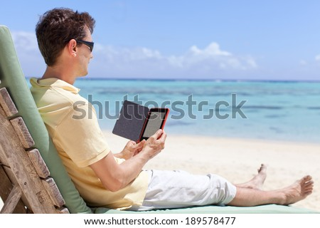 handsome man at the beach reading his electronic reader - stock photo