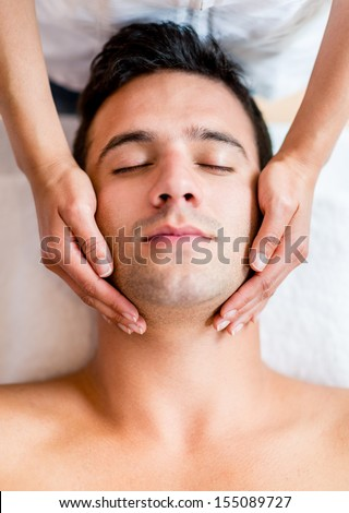 Handsome man at the spa getting a facial  - stock photo