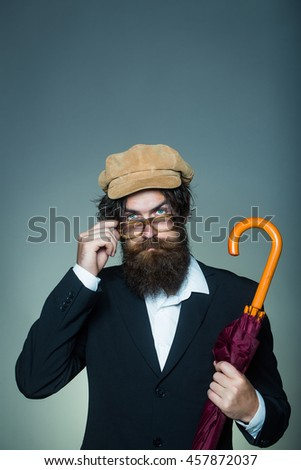 Handsome man bearded hipster male wears vintage cap glasses black suit with umbrella cane on grey wall - stock photo